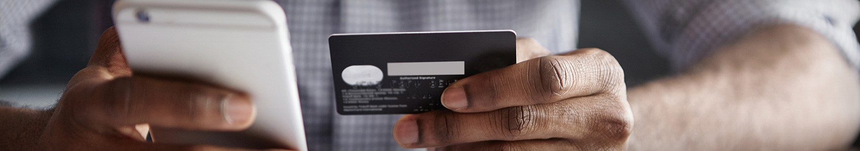 Man entering credit card information into mobile device